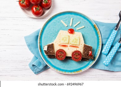 Funny sandwich with cheese and vegetables in a shape of police car, meal for kids idea, top view