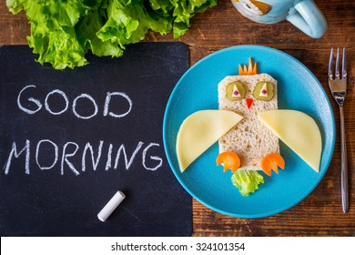 Funny sandwich owl for kids on plate, black chalkboard with Good morning greeting. healthy breakfast. Wooden table background
