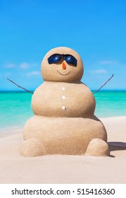 Funny sandy snowman in black sunglasses and carrot nose at tropical ocean beach. Holiday concept for New Year and Christmas travel destinations to hot coastal countries.