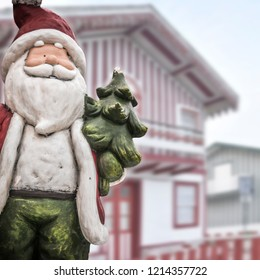 Funny Santa Claus in christmas scene with colorful houses