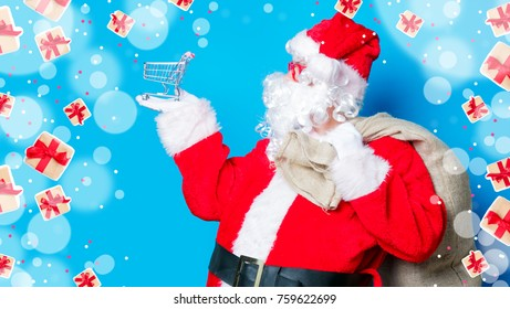 Funny Santa Claus have a fun with shopping cart on blue background