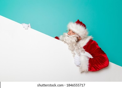 Funny Santa Claus holding a blank cardboard piece, isolated on mint colored background. Winter sales or New Year's Eve party invitation