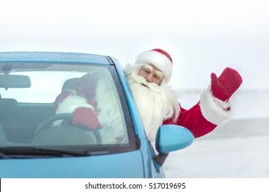 Funny Santa Claus peeking out of the car and congratulating waving