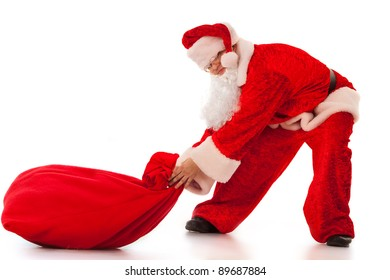 15b8e385e7 Funny Santa Clause pulling a heavy sack with gifts. Isolated on white.