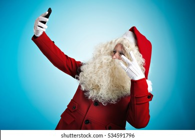 Funny Santa in fashionable coat takes selfie on his new mobile smart phone showing East side gesture , isolated on blue background