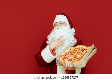 Funny Santa in red suit stands with pizza box with delivery on red background, looks into camera and strokes beard. Pizza for Christmas. Santa loves pizza.