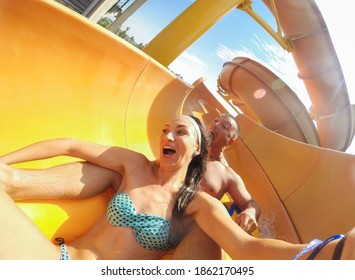 Funny scared couple on extreme water slide in aqua park