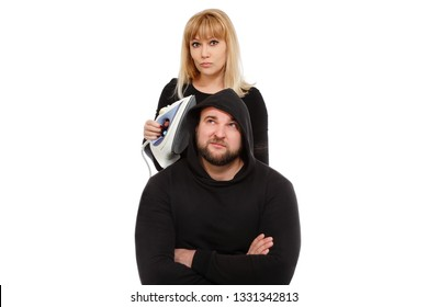 A funny scene. The blonde with the iron costs over the guy in a jacket with a hood. Happy couple of young people on a white background. meme Funny picture. Picture as a famous meme. Funny young people
