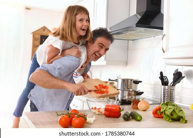 Funny scene of man cooking and daughter on their backs in the kitchen at home