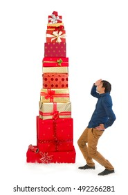 Funny scene of a young man looking up to a huge pile of christmas presents