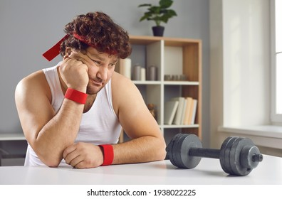 Funny sceptic lazy curly man looking thoughtfully at small barbell unsure whether he needs sports exercise. Sad fat man afraid of failure has no motivation to start training with dumbbells at home