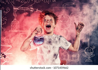 Funny schoolboy doing experiments in the laboratory. Explosion in the laboratory. Science and education.