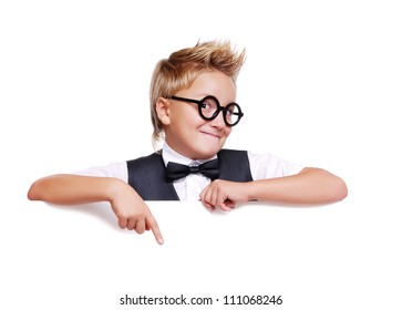 Funny schoolboy in glasses holding the blank board pointing on it with finger