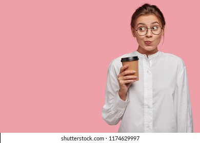 Funny schoolgirl with mysterious look, purses lips, wears round spectacles and white shirt, drinks takeaway coffee, stands against pink background with copy space for your promotional content