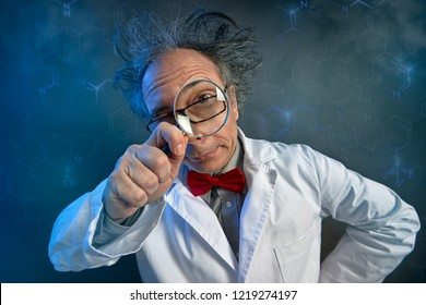 Funny scientist in white coat looking through a magnifying glass