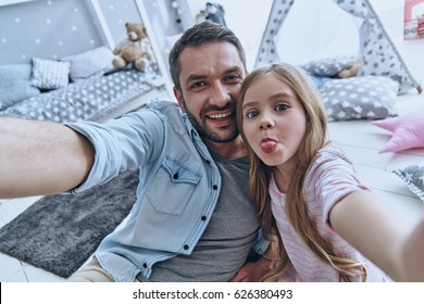 Funny selfie with dad. Self portrait of young father and his little daughter taking selfie while sitting on the floor in bedroom