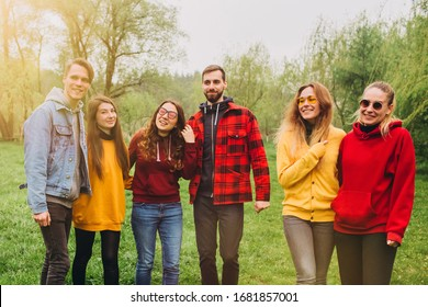 Funny selfie with friends. company of cheerful friends making selfie and smiling while standing outdoors. people wear red and yellow jumpers. young people resting in nature, talking and laughing