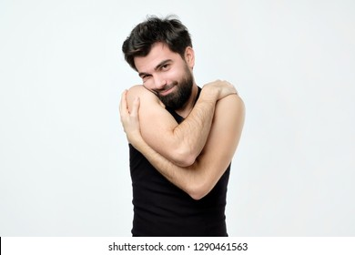 Funny selfish hispanic guy in black shirt cuddling himself and smiling