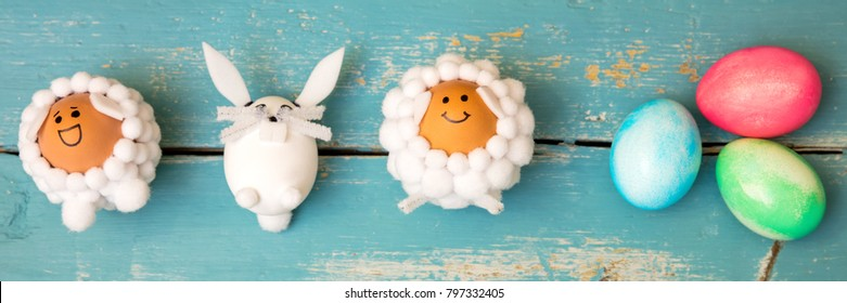 Funny selfmade animal shaped figures and colorful easter eggs on wooden background, flatlay