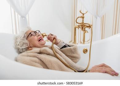 Funny senior lady with fur coat in bathtub