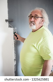 Funny senior man with beard painting the wall
