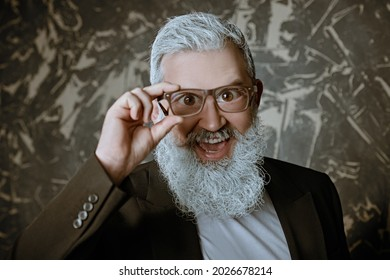 Funny senior man with a gray beard looks through glasses with big eyes and smiles on a grunge background. Vision and glasses concept.