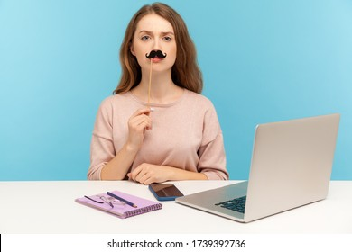 Funny serious woman office employee sitting at workplace, covering lips with fake paper moustache, imitating strict boss, humorous masquerade accessory. indoor studio shot isolated on blue background