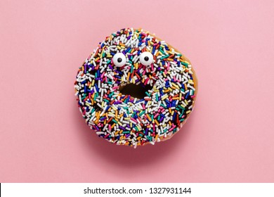 Funny shock face chocolate donut with sprinkles on a pastel pink background, creative minimal food concept, doughnut isolated on colorful background
