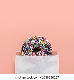 Funny shock face chocolate donut with sprinkles on a pink background, creative minimal food concept