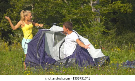 Funny shot of young couple arguing while setting up their tent on a sunny day. Annoyed girlfriend argues with her boyfriend while they set up their campsite by the forest. Young newlyweds fighting.