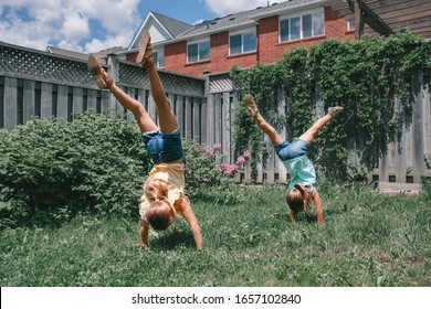 Funny sisters girls doing cartwheel on backyard. Excited joyful kids playing outdoor. Happy lifestyle childhood and freedom spirit concept. Seasonal sport activity for children.