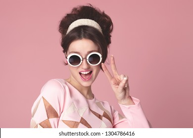 Funny sixties style girl with sunglasess on pink background.