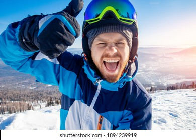 Funny skier man is taking selfie photo at wintertime in snow on mountain. Concept active trip in resort.