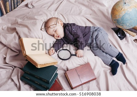Funny sleeping baby in glasses with books and globe layout.