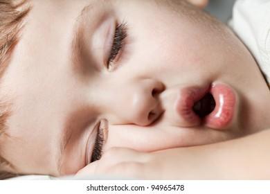 Funny sleeping little cute human child boy closed eyes face