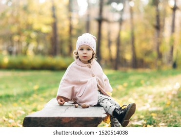 Funny small pretty girl in park,outdoor.Autumn time.Fashionable baby is sitting on the banch.