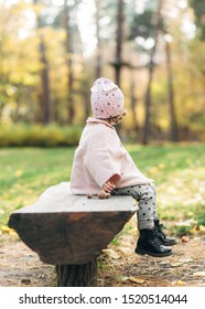 Funny small pretty girl in park,outdoor.Autumn time.Fashionable baby is sitting on the banch.Romantic moment.