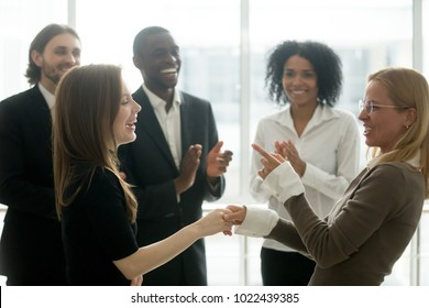 Funny smiling businesswomen holding hands celebrating success while diverse team applauding, female executive handshaking congratulating employee with common goal achievement, women power in business