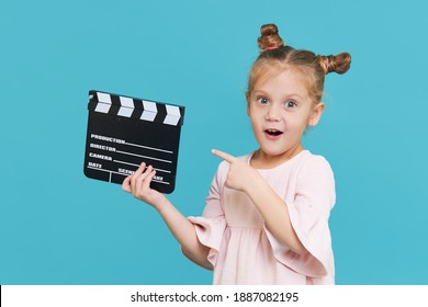 Funny smiling child girl hold film making clapperboard isolated on blue background. Little clipmaker, acting training. Funny face. Copy space for text.