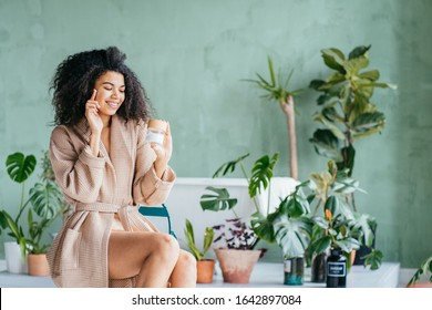 Funny smiling eco friendly african young woman in bathrobe apply cream on face, hold cream jar point finger at copy space advertise healthy dry skin care moisturizing beauty spa treatment concept.