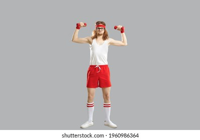 Funny smiling hipster skinny young guy in red and white sportswear standing and doing workout with dumbbels feeling tired over light grey wall background. Funny active sport lifestyle of man concept