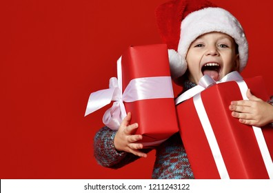 ea7bfce94407c Funny smiling joyful child boy in Santa red hat holding Christmas gift in  hand over the