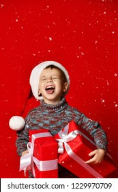 Funny smiling joyful  child boy in Santa red hat holding Christmas gift in hand and  stuck out his tongue from pleasure over the red background