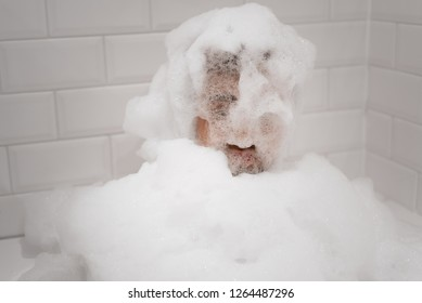 A funny, smiling man is completely covered in bubbles from a bath in tub, with no part of his head, face, or body without bubbles.