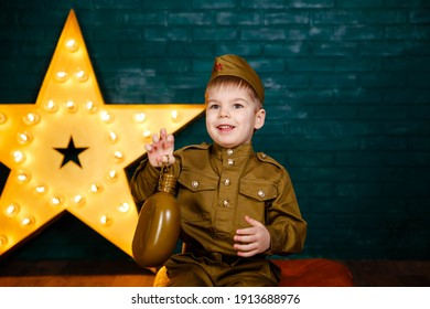 Funny smiling preschooler boy in military uniform. Young soldier. Little patriot. Army thee kid. Boy playing soldier. Portrait of happy young boy in camouflage. Military and rescue operation concept.