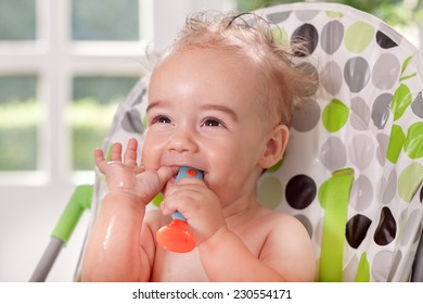 Funny smiling ragged baby putting spoon in to mouth
