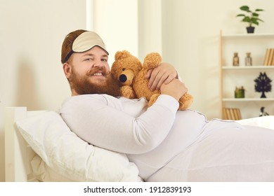 Funny smiling red haired bearded overweight man in white pajamas and sleeping mask lying with toy teddy bear in comfortable bed at home with room interior background. Funny male look concepts