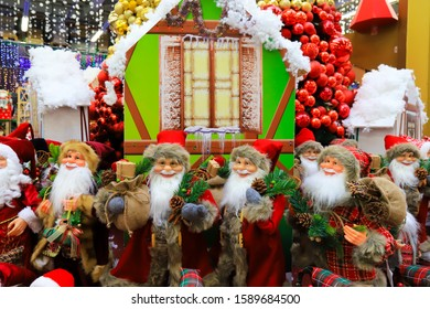 Funny smiling Santa Claus, a lot of favorite beautiful New Year and Christmas toys, many decorations and gifts, the best positive emotions. Festive Christmas winter trade 2020, shopping. Toy Store