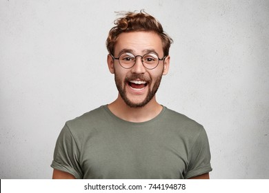 Funny smiling unshaven male wonk wears round spectacles and casual clothes, being glad to recieve interesting book as present, expresses positive emotions. People, happiness, positiveness concept