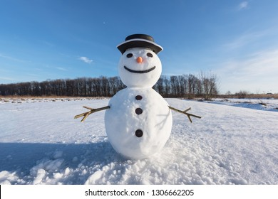 Funny snowman in black hat on snowy field. Christmass and New Year background